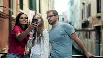 stock-footage-three-tourists-friends-taking-a-photo-with-smartphone-in-venice